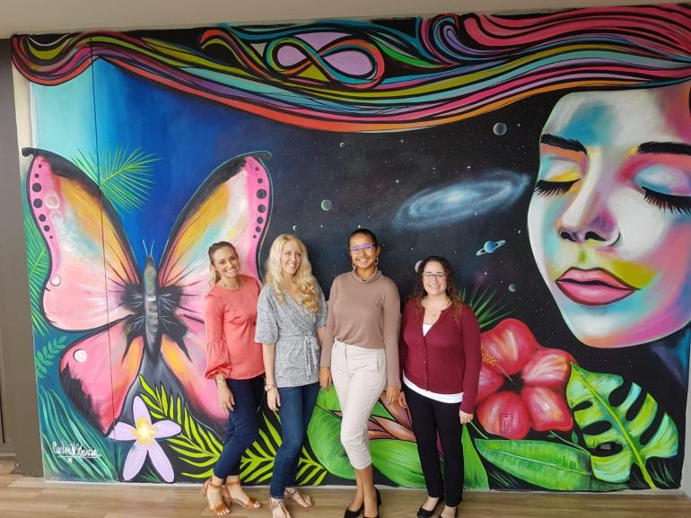 four-women-in-front-of-a-mural-at-kimpton-seafire-cayman